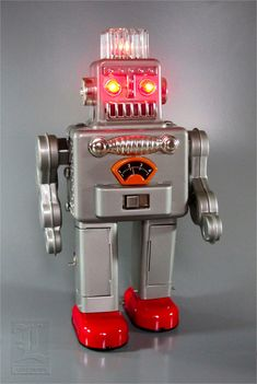 The robot walks forward with the multi-colored lights in its plastic dome spinning around. It stops, and while its eyes light up, it breathes out puffs of smoke! Vintage Robots, Retro Robot, Retro Toys, Vintage Toys, Arte Robot, I Robot, Atomic Decor, Robot Monster, Space Toys