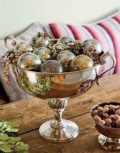 Silver bowl of ornaments on a rustic table.