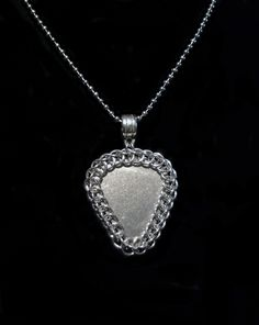 This stainless steel guitar pick is wrapped in Chain Maille (jewelry-grade Bright Aluminum), intricately crafted by yours truly!   Both sides of the pendant are identical.  32mm wide x 47 mm long (including bail), this this pendant makes a bold statement!  This comes on an 18 inch ball chain.  Cu...