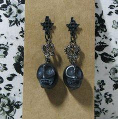 Par de brincos com caveira negra em pedra talhada e coroa grafite. R$ 12,90