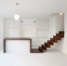 wood ribbon kitchen island - Created by KHBT (images by Johannes Marburg) and set in London, this lovely flat is modest and minimalist in almost every way – simple white surfaces from floor to wall to ceiling, and toned-down details … except for one wonderfully-warm stretch of wood that winds throughout.