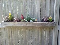Reuse old ply wood to make a planter box to hang on the fence