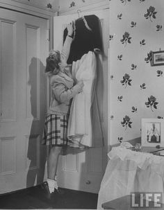 Long Island teenager Irma Olswang hanging up her first long party dress on door of bedroom closet. (The photograph on the table is of Irma's brother serving in the Navy). 1943