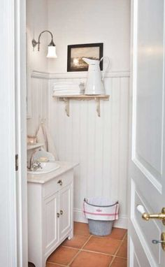 Love this look for my powder room in my dream farmhouse - especially love the terra cotta colored tile floor and the vanity light.