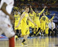 The Michigan bench celebrates a play in the first half during the 2013 NCAA championship game between Michigan and Louisville at the Georgia Dome in Atlanta on Monday, April 8, 2013.