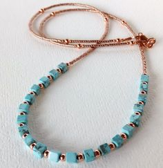 Copper and turquoise beaded necklace  Youll be in true boho style when you wear this copper and turquoise howlite layering necklace by Tam Davis. Designed with 4 mm turquoise colored howlite cube beads, copper plated round beads and Miyuki Delica seed beads. Its 22 inches in length, a perfect longer layering length. Copper plated lobster claw clasp.  Comes packaged in a decorated gift box.