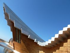 """""""Bodegas Ysios Winery"""": Named for the Egyptian gods Isis and Osiris, the sinusoidal shapes of this iconic winery in Rioja region of Spain mimic the mountains behind it. The Southern facade (shown here)  is clad in cedar slats to resemble wine barrels when reflected in in the pools below. Design: Santiago Calatrava, 2000 Photo: Andrew Forbes"""