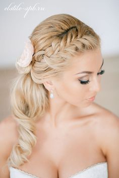 Wedding hairstyle with a braid and long loose curls.