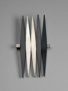 Brooch (1953) Betty Cook. Silver, black Plexiglas. Five elongated diamond shapes with sterling silver on one side and black Plexiglas on the reverse side, revolving around a central horizontal rod with a cubical post element at each end; the diamond elements can be arranged in any pattern by the wearer.