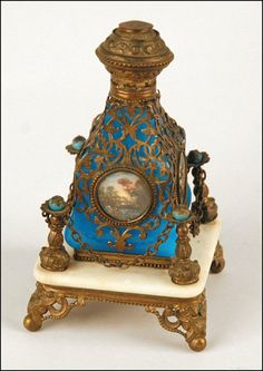 ANTIQUE GLASS PERFUME BOTTLE WITH PAINTED RONDELES DEPICTING LANDSCAPES, BRASS MOUNTS, AND SET IN A MARBLE AND BRASS STAND.