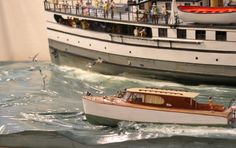 Closeup view showing cabin cruiser passing S.S. NOBSKA. Having the wood-carved seabase painted over lends realism to the water effect. To view images visit https://www.facebook.com/rex.stewart3/posts/10209097471854593.