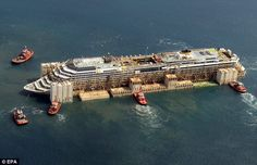 An aerial view as the Costa Concordia as it is dragged into the harbour of Genoa.