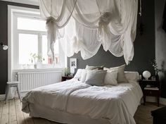 Bedroom with white sheets and dark walls