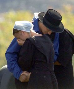 In this Oct. 3, 2006, file photo, members of the Amish community embracer in Nickel Mines, Pa., near the scene of a mass shooting incident at an Amish schoolhouse.