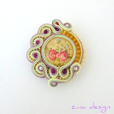 This one-of-a-kind soutache brooch in colors of light beige, green and mauve has a vintage rose glass cabochon, glass pearls, seed beads and crimson crystals. The brooch is approximately cm). Soutache Pendant, Soutache Necklace, Soutache Tutorial, Brooches Handmade, Handmade Necklaces, Passementerie, Polymer Clay Charms, Vintage Roses, Light Beige