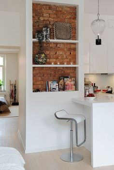 czerwona cegła wewnątrz otwartych białych szafek w małej kuchni - Lovingit.pl