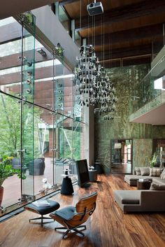 Fantastic Dark Brown Living Room With Glass Windows And Chandelier On Modern House Design