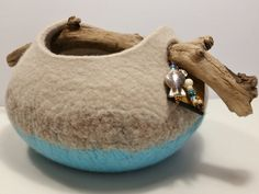 This vessel (or container) was hand felted using wet felting methods and features a handle made from a natural driftwood branch gathered from