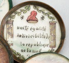 Bouton d'habit d'homme, monture en cuivre, orné d'un dessin polychrome peint sur verre représentant deux faisceaux de licteur, entourant l'inscription « Unité Egalité Indivisible de la République ou la Mort », surmontée d'un bonnet phrygien. Période Révolutionnaire. Diam.: 3, 5 cm.  Bibliographie : voir en référence un modèle dans le même style, dans le catalogue de l'exposition « Mode & Révolution (1780-1804) », Musée Galliera, du 8 février au 7 mai 1989, p. 164/165.
