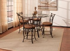 Seat your guests in style with this Carley 5-piece glass counter-height dining set. It offers a light, sophisticated look in golden brown, compliments of its chic metal cabriole legs and beautiful scroll-inspired stool backs. Plus, perfect for fans of after-dinner conversation, the stools' circular footrests, swivel and padded seats add comfort while you dine.