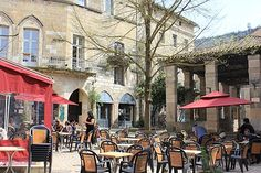 Cafe and old halle in St Antonin Noble Val. Holiday rental apartment '17 Place de la Halle' in the background, overlooking the square.