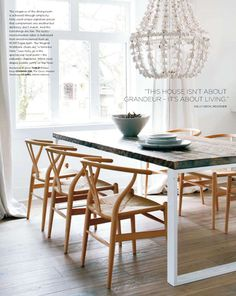 reclaimed wood from rcmp horse barn for tabletop + wishbone chairs + craft chandelier in dining room by kelly deck via style at home