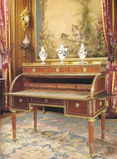 The circa 1780 bureau a cylindre (roll-top desk) by Claude-Charles Saunier in the Grand Bureau is typical of the Louis XVI style. It is made of oak with veneer panels of flame grain mahogany and ornamented with chased and gilt bronze mounts.