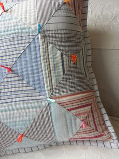 This pretty reversible patchwork cushion cover is made from recycled striped work shirts on one side with a more tailored looking reverse in a pretty pale peach linen, making it a sort of Town and Country cushion! The country side is patchwork made from machine pieced triangles, mostly in recycled cotton work shirt fabrics in blue and grey stripes, with a few modern stripes in pinks and turquoise added. It has been hand quilted and then tied with brightly coloured tufts of embroidery…