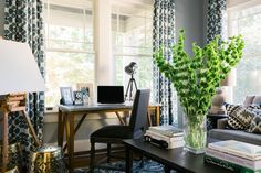 This blue-gray multipurpose office space features a desk area with gray upholstered wooden chair, coffee table with greenery in a vase, and patterned blue-and-white curtains.
