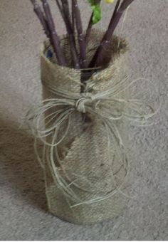 I took a plain ol glass vase and hot glued burlap and a twine bow to it :)