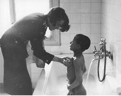 Policjantka kąpie chłopca przebywającego w Izbie Dziecka.