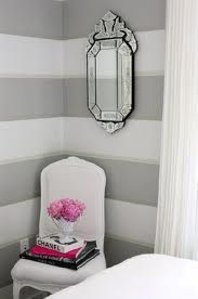 Grey striped walls, white bedding and hints of light pink