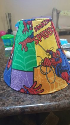 Lamp shade for boys room...extra curtain material,  a few clips to hold material in place to fit tight while you brush on the mod podge and voila!