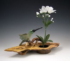 Ship Date: 2-4 weeks Ikebana vase, carved clay slab with sculpted branches and Hummingbird. Air brushed and smoke fired finish. Water cup with pin frog to hold flowers. Teal, green and sunset colors a