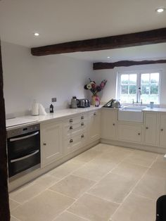 The pale cream and gentle olive undertones of our Worn Ivory Sandstone look perfect in this country cottage kitchen. The neutral scheme gives such a calm, peaceful atmosphere to this room.