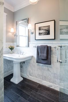 The smooth lines on the dark wood flooring pair beautifully with the marble wall tiling in this traditional bathroom. Two small mounted lamp fixtures frame the mirror above the pedestal sink. A glass door for the shower continues the bright, open feel of this room.