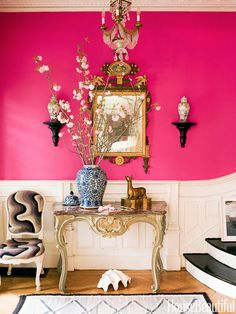 The entry of a late-19th-century house in Brooklyn is a showstopper, with walls in Benjamin Moore's Razzle Dazzle. The table and side chair — covered in vintage needlepoint — are Louis XV, and the mirror is 18th-century Italian. Designed by Jonathan Berger.
