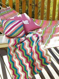 Pute og pledd i sommerlige farger. Et lunende pledd og en god pute til å ha i ryggen eller under hoder er kjekt å ha både i hagemøblegruppa, hengekøya eller innendørs.