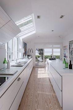 Construite en longueur et habillée de meubles laqués blanc, cette cuisine est baignée de lumière
