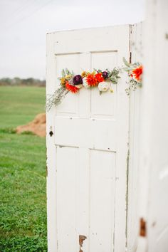 old doors decorated with florals used as the ceremony focal point Photography: Firm Anchor - www.firmanchor.com  Read More: http://www.stylemepretty.com/southeast-weddings/2014/04/23/colorful-vineyard-wedding-in-the-rain/