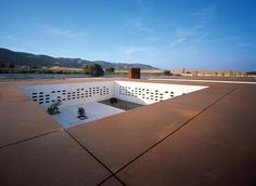 The building is structured around a series of patios. The main one (shown here) is animated by a long, reflecting pool