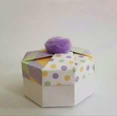 ORIGAMI OCTAGON BOX. Pom poms are great little toppers for octagon or hexagon origami boxes. I used scrapbook paper in color coordinated patterns for the top of the box. The color pallette of lavender, mint green and yellow makes a great combination. The bottom is made from a white cardstock and is a traditional handcrafted octagon box allowing for more room inside the box.  #whimsical packaging #origami octagon box #box #packaging #origami #favor packaging #gift #gift box #favor box…