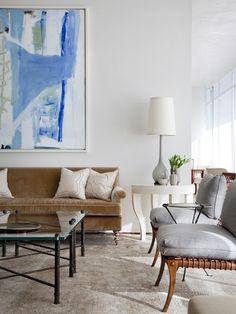 Sofá em veludo caramelo combinado com poltronas em tecido cinza claro e madeira. Toques de azul no quadro.
