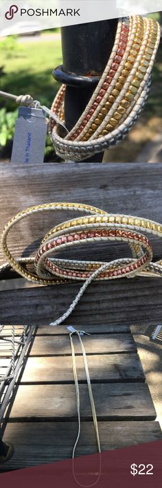 Nakamol Handmade Leather Wraparound Bracelet Tiny rose, silver and yellow colored brass beads have been hand woven between white leather strings for this wrap around bracelet style.  Can be wrapped around 5 times on a 7-inch wrist.  The bracelet has a 3-position adjustable closing.  I wear mines as a 22-inch necklace.  This item is brand new, never been worn. Nakamol Jewelry Bracelets