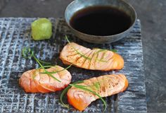 Serve flash-seared salmon slices with aromatic yuzu dipping sauce as an appetizer.