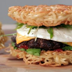 1 package ramen noodles 2 eggs, divided 2 tablespoons neutral oil, such as canola or grapeseed 1 tablespoon ketchup 1/2 tablespoon sriracha 1 beef burger patty Soy sauce Sesame oil 1 slice American cheese 1 scallion, thinly sliced on the bias 1/2 cup arugula