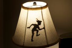 """Newest addition to the """"Disney Den"""": We printed a silhouette of Peter Pan, cut it out, and podge podged it to a small lamp that we already had. It looks so great, and the lamp shade is thick enough that Peter is not visible when the light is off!"""