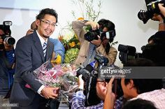 Figure skater Daisuke Takahashi receives a flower bunch during a press conference on October 14 2014 in Okayama Japan