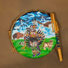 Painted Drum - Artist: Monty Brill, Lakota -Monty has painted a beautiful and colorful picture on this 11.5 inch drum. The 12 inch drum stick is covered with leather and has bead work. #nativeamerican #music #instrument #painted #Painteddrum #lakota #powwow #aktalakotamuseum Native American Instruments, Cultural Significance, Pow Wow, Colorful Pictures, Thing 1 Thing 2, Drums, Art Gallery, Bead, Museum