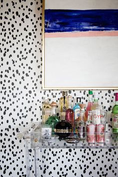 Kime, who has a visual arts degree, painted the blue-and-white abstraction that hangs above the Lucite bar cart.